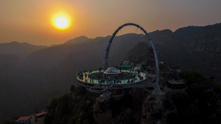 This photo taken on April 30, 2016 shows a glass sightseeing platform in Shilinxia scenic spot in Pinggu District of Beijing.  The sightseeing platform, which hangs 32.8 meters out from the cliff, is claimed to be the largest glass sightseeing platform in the world. / AFP PHOTO / STR / China OUT