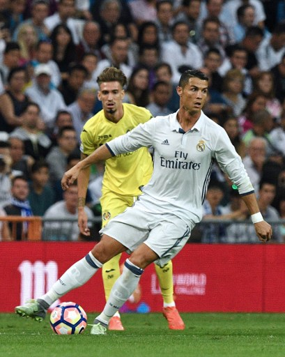 Real Madrid's Portuguese forward Cristiano Ronaldo (R) vies with Villarreal's midfielder Samuel Castillejo during the Spanish league football match Real Madrid CF vs Villarreal CF at the Santiago Bernabeu stadium in Madrid on September 21, 2016. / AFP PHOTO / GERARD JULIEN