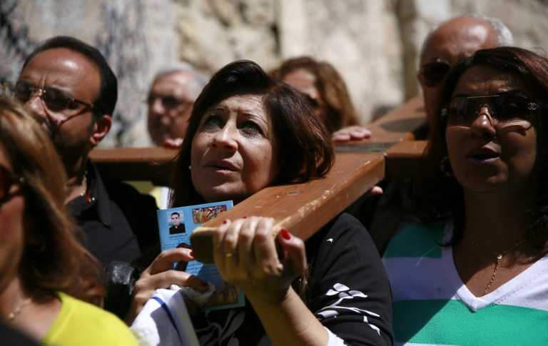 Catholic pilgrims carry a wooden cross along the Via Dolorosa (Way of Suffering) in Jerusalem's Old City during the Good Friday procession on April 3, 2015. Many Christian pilgrims took part in processions along the route where according to tradition Jesus Christ carried the cross during his last days. AFP PHOTO / GALI TIBBON / AFP / GALI TIBBON