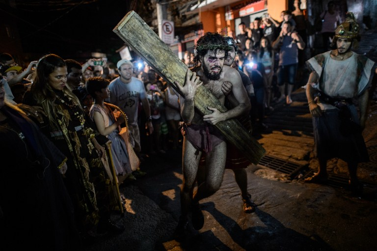 Catholic devotees reenact the sufferings of Jesus Christ during a Good Friday procession on a street in the Rocinha community (favela) of Rio de Janeiro, Brazil, on April 3, 2015. People around the world participate in ceremonies evoking the day that Jesus Christ was crucified. AFP PHOTO / YASUYOSHI CHIBA / AFP / YASUYOSHI CHIBA
