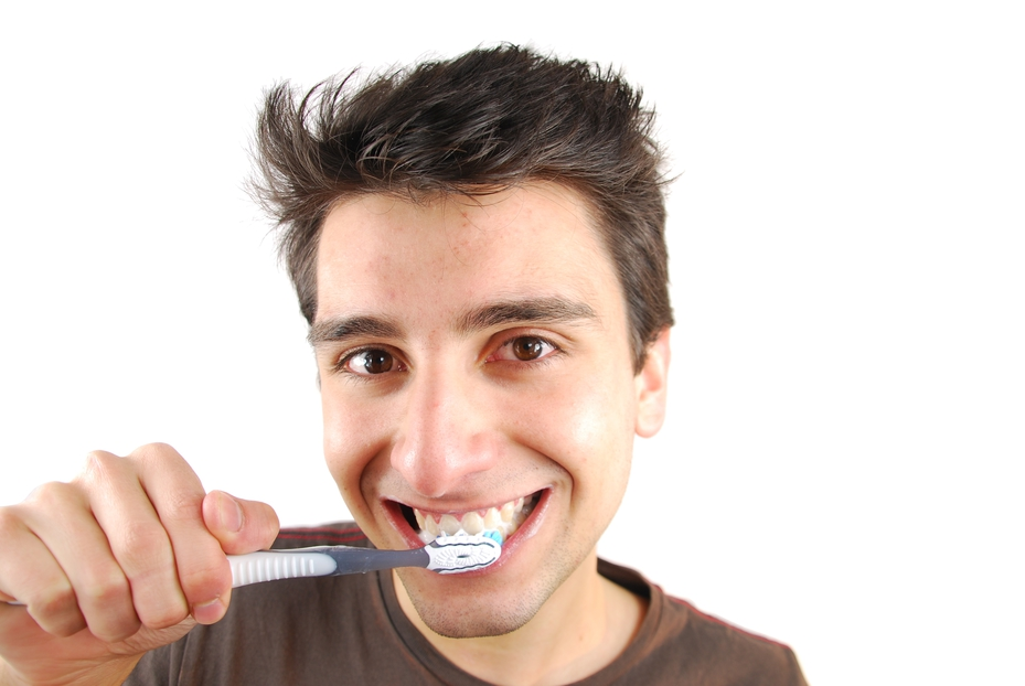 cheerful young man is washing teeth over white background