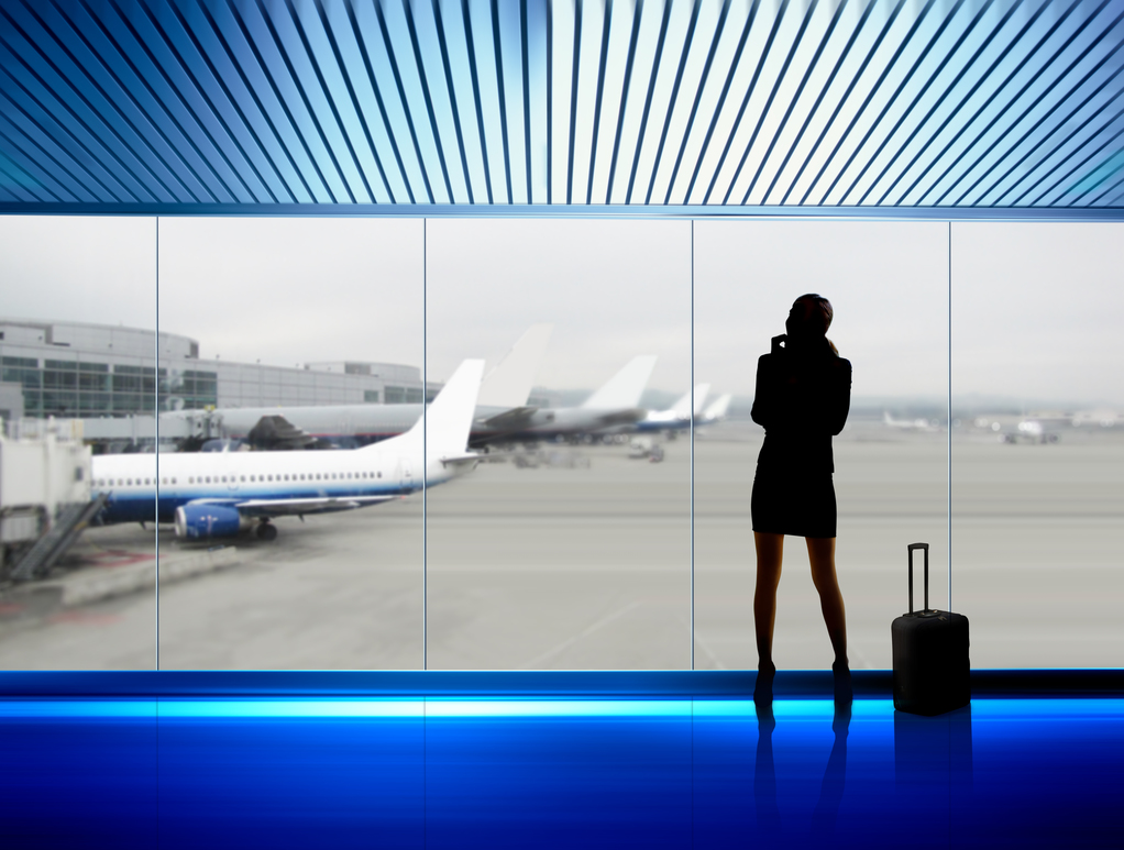 silhouette of businesswoman which expects flight aboard the plane in airport