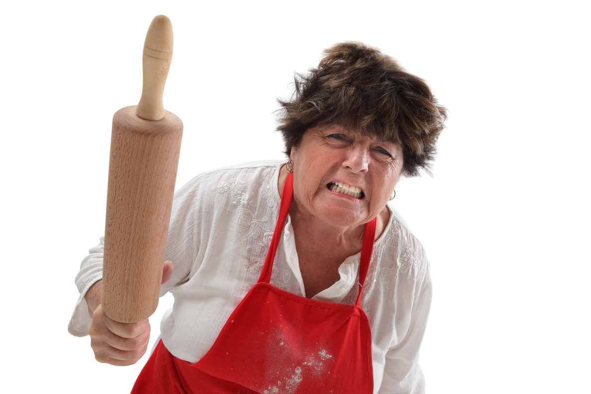Photo of an angry old woman threatening with a rolling pin.