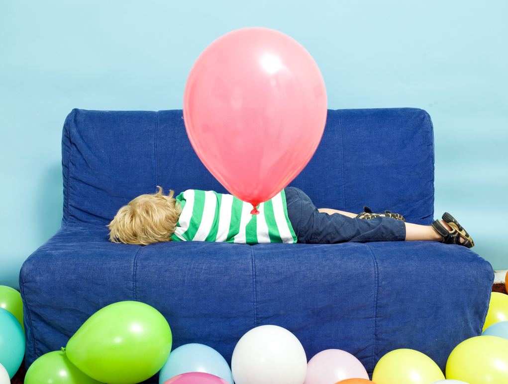 Young Boy lying down on a couch on his birthday