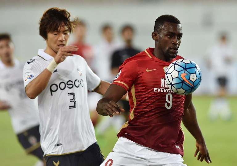 Jackson Martinez of Guangzhou Evergrande (R) fights for the ball with Kim Kwangsuk of Pohang Steelers during their AFC Champions League group stage football match in Guangzhou, in southern China's Guangdong province on February 24, 2016. CHINA OUT    AFP PHOTO / AFP PHOTO / STR